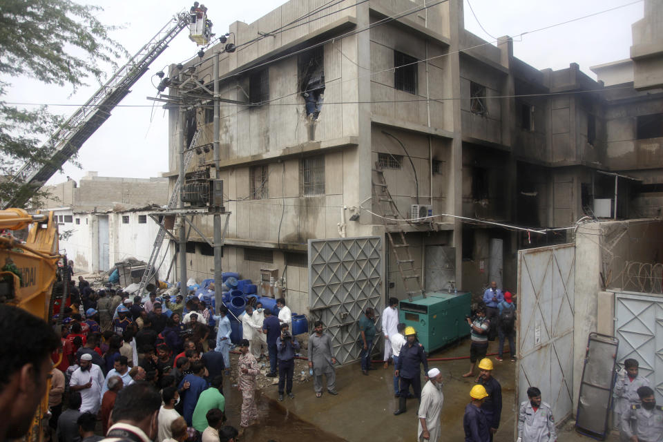 Rescue workers search bodies at the site of a burnt chemical factory, in Karachi, Pakistan, Friday, Aug. 27, 2021. A massive fire broke out at a chemical factory in Pakistan's southern port city of Karachi on Friday, killing some workers and injuring several others, police and a government spokesman said. (AP Photo/Ikram Suri)