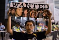 A man holds a poster with images of police officers suspected of being involved in beating up a pro-democracy protester, Hong Kong on October 15, 2014 (AFP Photo/Alex Ogle)