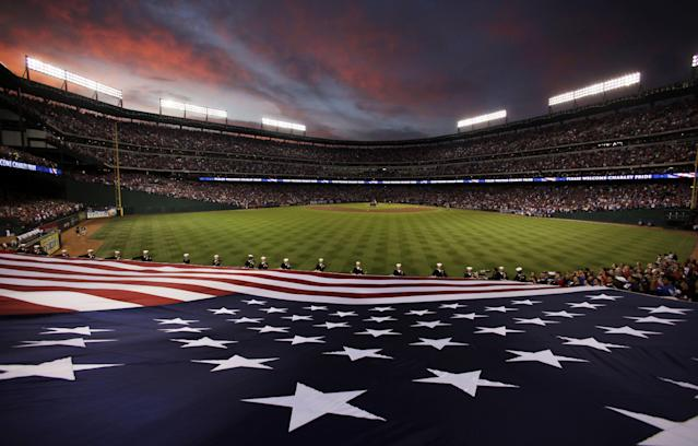 FILE - This Nov. 1, 2010 file photo shows the U.S. flag being held by sailors before Game 5 of baseball's World Series between the San Francisco Giants and the Texas Rangers, in Arlington, Texas. A perfect game, MLB's first-ever interleague game and consecutive World Series for the Texas Rangers. Those are some of the highlights at their home stadium, which Friday, April 11, 2014, marks the 20th anniversary of its first regular-season game.(AP Photo/Eric Gay, File)
