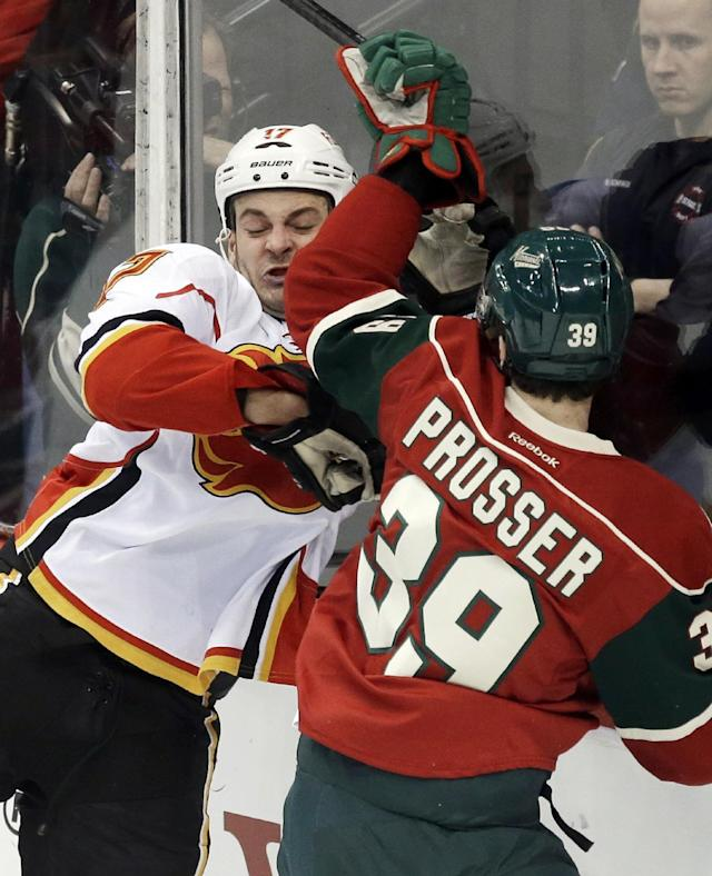 Calgary Flames' Lance Bouma, left, gets checked into the boards by Minnesota Wild's Nate Prosser in the first period of an NHL hockey game, Monday, March 3, 2014, in St. Paul, Minn. (AP Photo/Jim Mone)