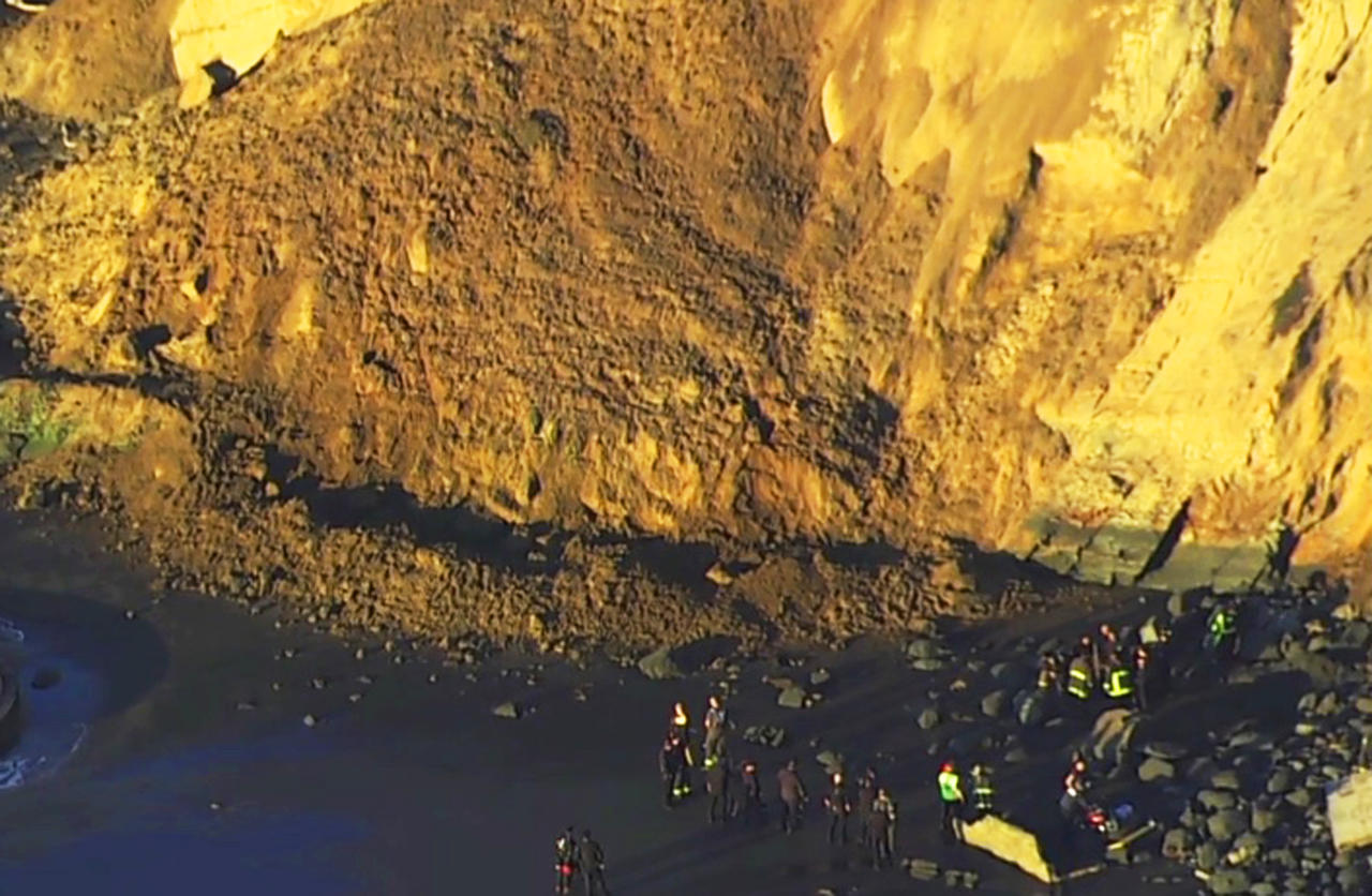 This photo from video provided by KGO-TV shows firefighters searching for a person who was thought to be buried by a landslide near a San Francisco beach Friday, Feb. 22, 2019. San Francisco Fire Department spokeswoman Mindy Talmadge said two people were walking along the shoreline when a cliff and hill gave way. (KGO-TV via AP)