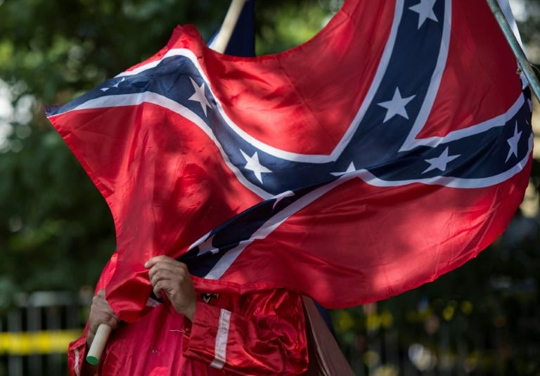 In this file photo taken July 8, 2017, a member of the Ku Klux Klan holds a Confederate flag  during a rally in Charlottesville, Virginia; the Pentagon has banned the display of that flag on US military bases