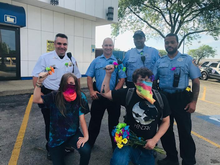 At the June Black Lives Matter demonstration, Edgar Ascencio of Joliet and Olivia Walker of Minooka pose for photographs with the group of Joliet police officers who were appreciative of their kindness and friendly tone during the protest. Image via John Ferak/Patch