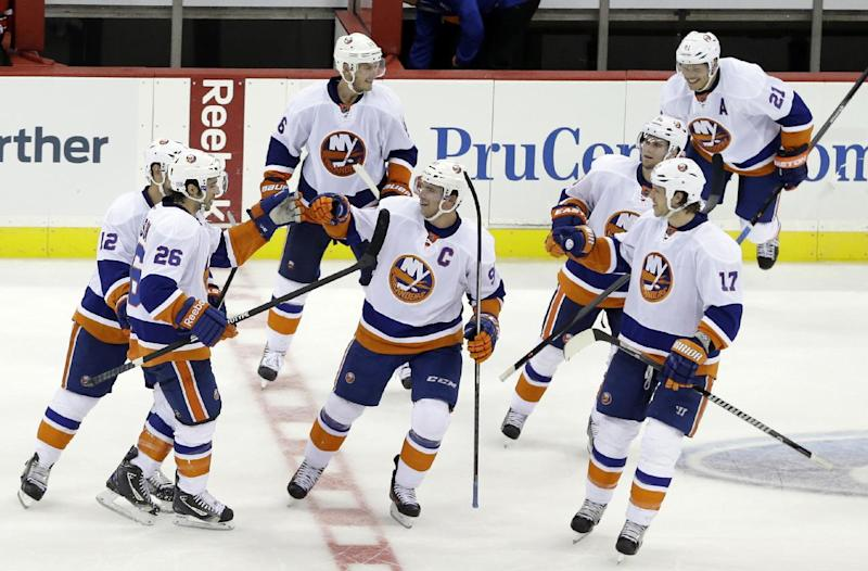 New York Islanders' Matt Moulson (26) is congratulated by teammates after scoring in the shootout to give the Islanders a 4-3 win over the New Jersey Devils in an NHL hockey game, Friday, Oct. 4, 2013, in Newark, N.J. (AP Photo/Julio Cortez)