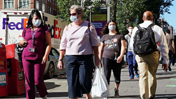 PHOTO: NEW YORK, NEW YORK - JULY 14: People walk while wearing protective masks as New York City moves into Phase 3 of re-opening following restrictions imposed to curb the coronavirus pandemic on July 14, 2020. (Cindy Ord/Getty Images)