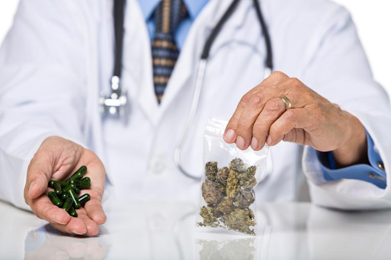 A physician with a stethoscope around his neck holding a baggie of cannabis in his left hand, and cannabis oil capsules in his right hand.