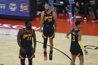 Golden State Warriors' Stephen Curry, center, yells after making a three-point basket with teammates Draymond Green, left, and Jordan Poole, right, during the first half of an NBA basketball Western Conference play-in game against the Memphis Grizzlies in San Francisco, Friday, May 21, 2021. (AP Photo/Jed Jacobsohn)