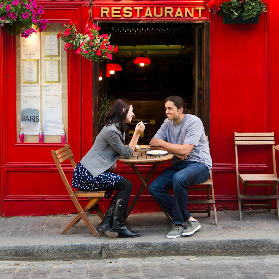 Young couple sitting in sidewalk cafe, Paris, France.