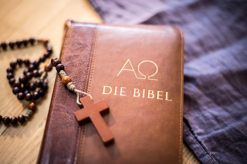 Holy bible and rosary are lying on a wooden desk