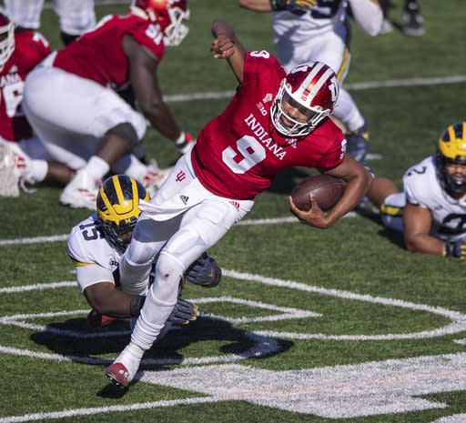 Indiana quarterback Michael Penix Jr. (9) is tripped up by Michigan defensive lineman Christopher Hinton (15) as he runs the ball out of the backfield during the second half of an NCAA college football game Saturday, Nov. 7, 2020, in Bloomington, Ind. Indiana won 38-21. (AP Photo/Doug McSchooler)