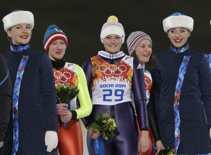 Germany's gold medal winner Carina Vogt, center, smiles as she is flanked by Austria's silver medal winner Daniela Iraschko-Stolz, 2nd left, and France's bronze medal winner Coline Mattel, 2nd right, after the flower ceremony of the women's normal hill ski jumping final at the 2014 Winter Olympics, Tuesday, Feb. 11, 2014, in Krasnaya Polyana, Russia. (AP Photo/Matthias Schrader)