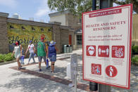 FILE - In this June 16, 2020, file photo, signs remind patrons to wear masks and other protocols because of the coronavirus pandemic as they stroll through the Disney Springs shopping, dining and entertainment complex in Lake Buena Vista, Fla. On Friday, June 26, Vice President Mike Pence said Americans should look to their state and local leadership for modeling their behavior during the coronavirus pandemic. The comments only days after President Donald Trump held two campaign events that drew hundreds of participants but few wearing masks. (AP Photo/John Raoux, File)