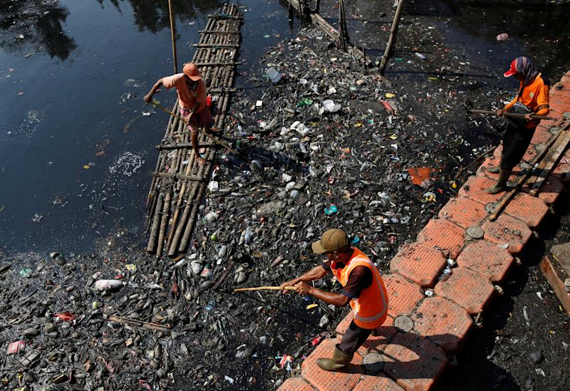 Government workers gather plastic and other debris for collection and disposal from the Sekretaris River in Jakarta, Indonesia. (Photo: Darren Whiteside/Reuters)