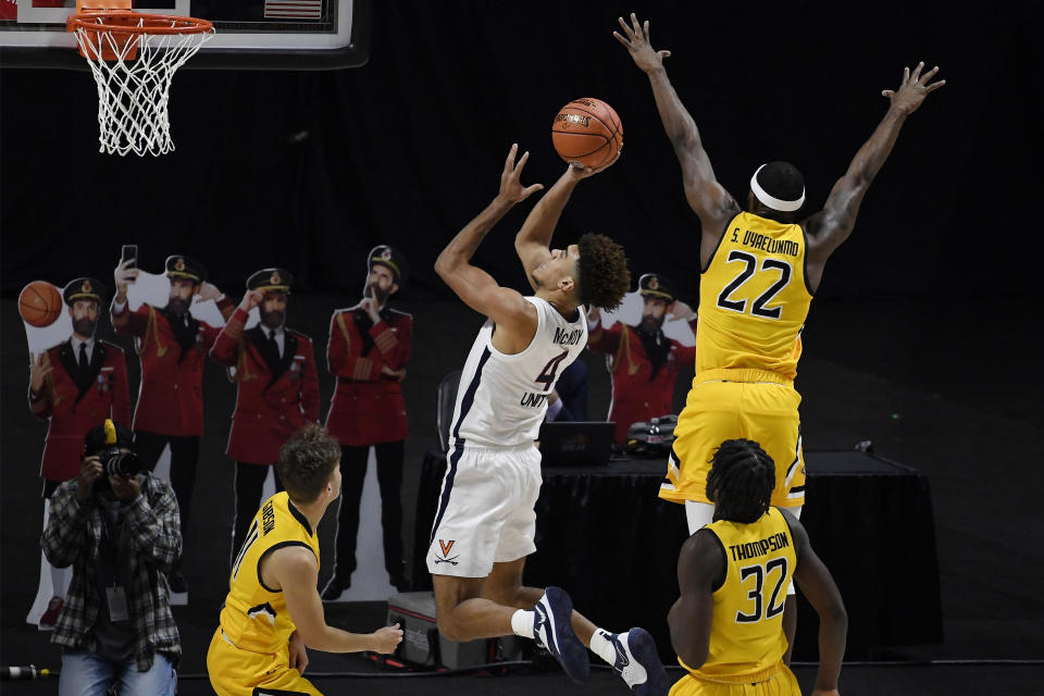 Virginia's Justin McKoy, center, shoots past Towson's Solomon Uyaelunmo, right, in the first half of an NCAA college basketball game, Wednesday, Nov. 25, 2020, in Uncasville, Conn. (AP Photo/Jessica Hill)