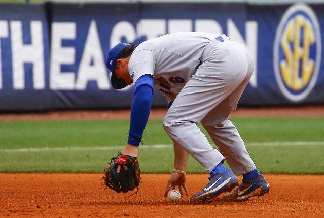 Florida third baseman Jonathan India bobbles the ball as he tries to field the hit by LSU's Zach Watson allowing another run to score during the sixth inning of a Southeastern Conference tournament NCAA college baseball game. Play resumed in the sixth inning after an overnight fog delay, Saturday, May 26, 2018, in Hoover, Ala. (AP Photo/Butch Dill)