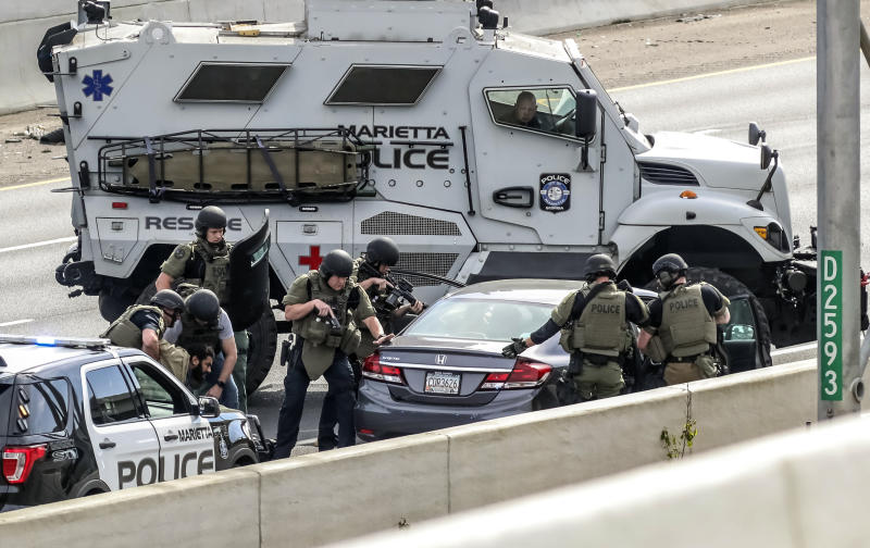 Marietta Police arrest a man after a standoff along the southbound lanes of Interstate 75, Friday, March 29, 2019, near Marietta, Ga., northwest of Atlanta. Marietta police said an armed driver had stopped on the freeway and wasn't cooperating with officers. Police had followed the vehicle to I-75 since it matched the description from an armed robbery nearby. (John Spink/Atlanta Journal-Constitution via AP)