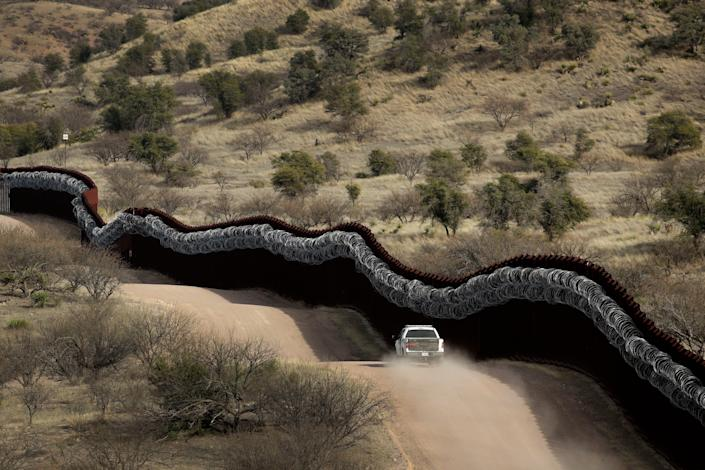 A Customs and Border Protection agent patrols the border wall east of Nogales, Ariz., in 2019.