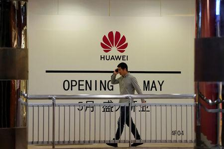 A man using his mobile phone walks past a yet-to-open Huawei store inside a shopping mall in Shanghai, China May 16, 2019.  REUTERS/Aly Song