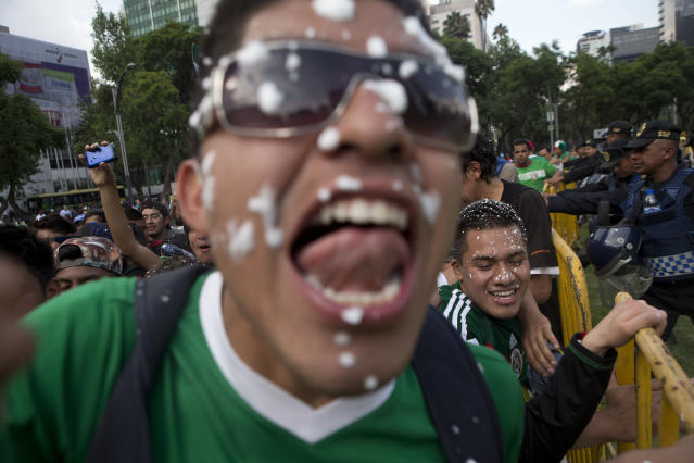 Mexico soccer fans celebrate at the Independence Monument after their team tied with Brazil in their 2014 World Cup soccer match, in Mexico City, Tuesday, June 17, 2014. Mexico claimed a deserved point against Brazil in a largely frustrating Group A game which finished 0-0 at Estadio Castelao in Fortaleza. (AP Photo/Rebecca Blackwell)