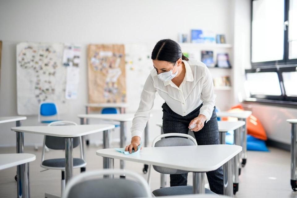 Teacher back at school after covid-19 quarantine and lockdown, disinfecting desks.