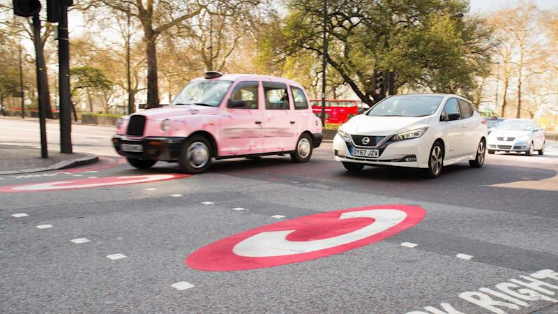 Ultra Low Emissions Zone sign on asphalt with Nissan Leaf and London taxi