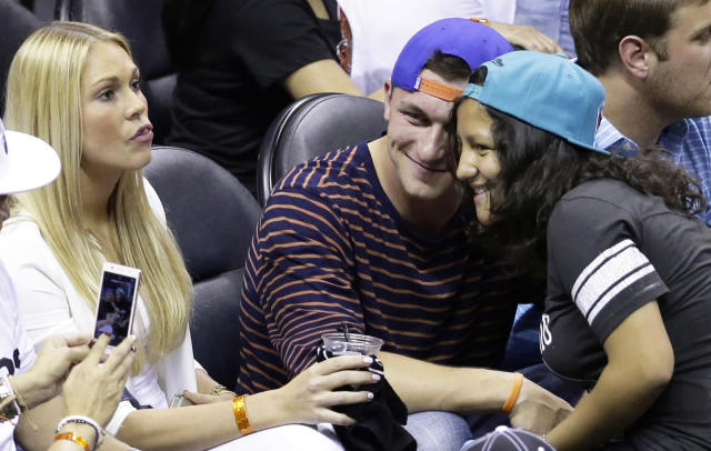 NFL football player Johnny Manziel, center, poses for a photograph during the second half in Game 2 of the NBA basketball finals between the San Antonio Spurs and the Miami Heat on Sunday, June 8, 2014, in San Antonio. (AP Photo/Tony Gutierrez)