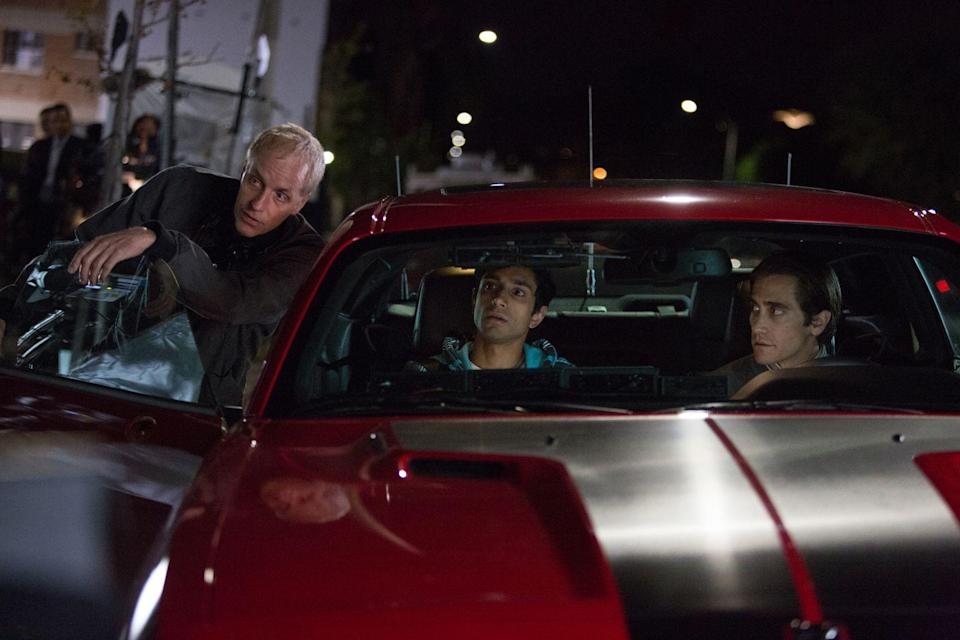 <p>Riz Ahmed and Jake Gyllenhaal sit in the front seat of a car as they speak with director Dan Gilroy between takes on <em>Nightcrawler. </em></p>