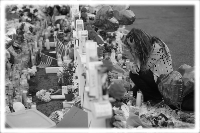 Gloria Garces kneels in front of crosses at a makeshift memorial near the scene of a mass shooting at a shopping complex Tuesday, Aug. 6, 2019, in El Paso, Texas. (Photo: John Locher/AP; digitally enhanced by Yahoo News)