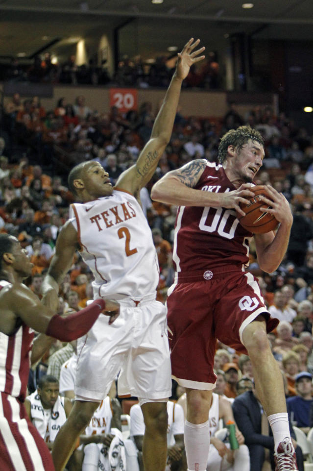 Oklahoma forward Ryan Spangler (00) comes down with a rebound against Texas guard Demarcus Holland (2) during the first half of an NCAA college basketball game, Saturday, Jan. 4, 2014, in Austin, Texas. (AP Photo/Michael Thomas)