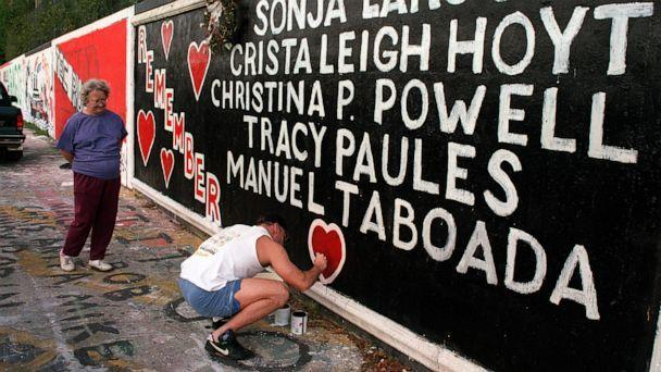 PHOTO: Tony Mekeel repaints one of the hearts on the 34th Street Wall memorial as Ann Garren, the mother of slain student Christa Hoyt, watches. Mekeel was a neighbor of one of the slain students, Manuel Taboada, during the ordeal in 1990. (Ilan Campbell/The Gainesville Sun-USA TODAY/Imagn)