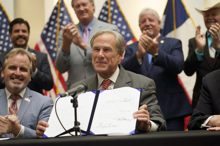 Texas Gov Greg Abbott shows off Senate Bill 1, also known as the election integrity bill, after he signed it into law in Tyler, Texas, Tuesday, Sept. 7, 2021. (LM Otero/AP)