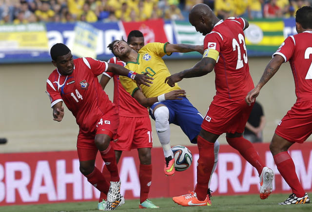 Brazil's Neymar, center, fights for the ball with Panama's Nahil Carroll, left, and Felipe Baloy, right, during a friendly soccer match at the Serra Dourada stadium in Goiania, Brazil, Tuesday, June 3, 2014. Brazil is preparing for the World Cup soccer tournament that starts on 12 June. (AP Photo/Andre Penner)