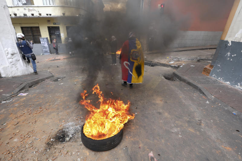 An anti-government demonstrator, wearing a national flag as a cape, stands by a burning tire during clashes with police in downtown Quito, Ecuador, Oct. 8, 2019. (Photo: Fernando Vergara/AP)