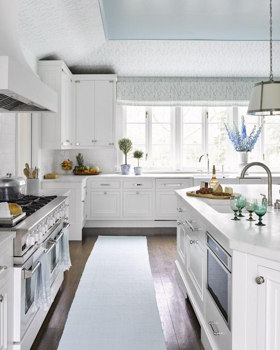 "<p>The unexpected addition of aqua on the ceiling and a blue-patterned wallcovering from designer <a href=""http://www.megbraffdesigns.com/home"" rel=""nofollow noopener"" target=""_blank"" data-ylk=""slk:Meg Braff's textile collection"" class=""link rapid-noclick-resp"">Meg Braff's textile collection</a> visually expands this <a href=""https://www.veranda.com/decorating-ideas/a27105023/meg-braff-long-island-home/"" rel=""nofollow noopener"" target=""_blank"" data-ylk=""slk:Long Island kitchen"" class=""link rapid-noclick-resp"">Long Island kitchen</a> by drawing the eye upward. Braff expanded and updated the cooking space with <a href=""https://www.vermontmarbleandgranite.com/"" rel=""nofollow noopener"" target=""_blank"" data-ylk=""slk:Danby"" class=""link rapid-noclick-resp"">Danby</a> marble counters and cabinetry in a pearly color from <a href=""https://www.finepaintsofeurope.com/"" rel=""nofollow noopener"" target=""_blank"" data-ylk=""slk:Fine Paints of Europe"" class=""link rapid-noclick-resp"">Fine Paints of Europe</a><u>.</u> The sink fixtures and hardware are by <a href=""https://www.waterworks.com/us_en/"" rel=""nofollow noopener"" target=""_blank"" data-ylk=""slk:Waterworks"" class=""link rapid-noclick-resp"">Waterworks</a>, and the pendant light is by <a href=""https://www.vaughandesigns.com/us/"" rel=""nofollow noopener"" target=""_blank"" data-ylk=""slk:Vaughan"" class=""link rapid-noclick-resp"">Vaughan</a>. The ceiling paint color is Picture Perfect by Benjamin Moore.</p><p><a class=""link rapid-noclick-resp"" href=""https://www.benjaminmoore.com/en-us/color-overview/find-your-color/color/743/picture-perfect?color=743"" rel=""nofollow noopener"" target=""_blank"" data-ylk=""slk:Get the Look"">Get the Look</a></p>"