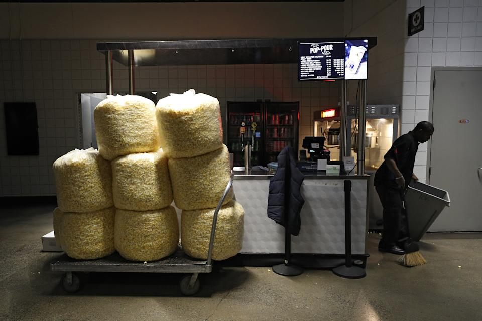WASHINGTON, DC - MARCH 12: Bags of popcorn rest on a cart as a man cleans behind a vendor kiosk prior to the Detroit Red Wings playing against the Washington Capitals at Capital One Arena on March 12, 2020 in Washington, DC. Yesterday, the NBA suspended their season until further notice after a Utah Jazz player tested positive for the coronavirus (COVID-19). The NHL said per a release, that the uncertainty regarding next steps regarding the coronavirus, Clubs were advised not to conduct morning skates, practices or team meetings today. (Photo by Patrick Smith/Getty Images)
