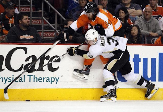 Philadelphia Flyers' Sean Couturier, top, and Pittsburgh Penguins' Olli Maatta battle for the puck along the boards during the second period of an NHL hockey game, Saturday, March 15, 2014, in Philadelphia. (AP Photo/Tom Mihalek)