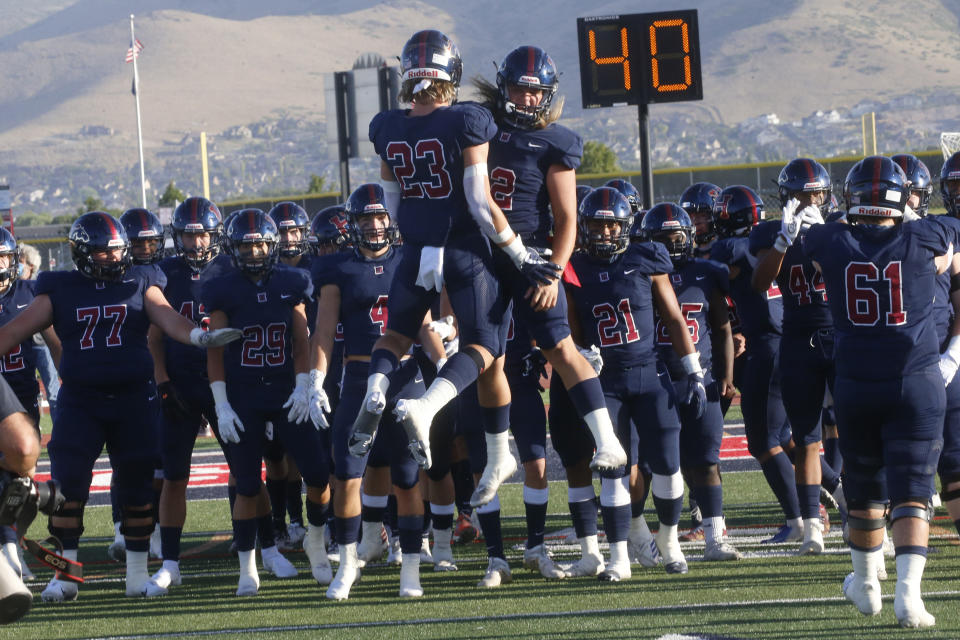Herriman players celebrate as they take the field for a high school football game against Davis, Thursday, Aug. 13, 2020, in Herriman, Utah. Utah is among the states going forward with high school football this fall despite concerns about the ongoing coronavirus pandemic that led other states and many college football conferences to postpone games in hopes of instead playing in the spring. (AP Photo/Rick Bowmer)