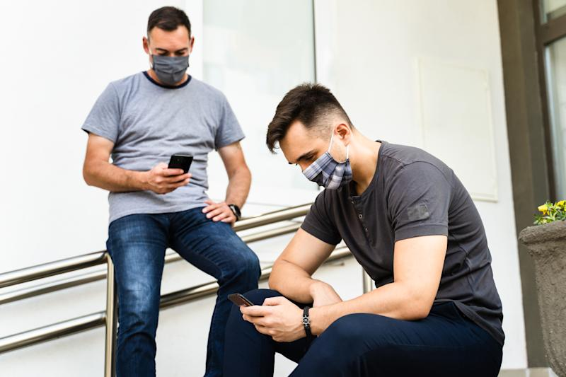 Two men in front of wall of building using mobile phone app wearing protective mask after lockdown - Maintaining social distance via internet network on travel vacation - New Normal lifestyle concept