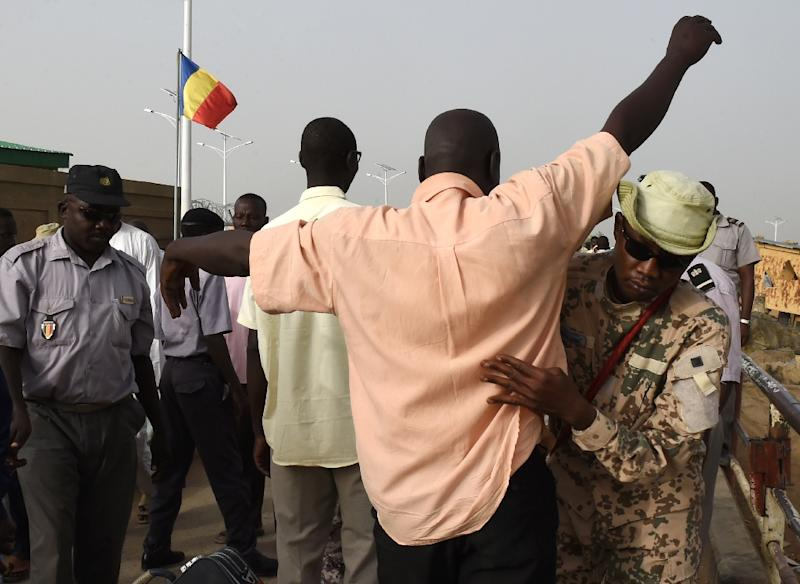 Chad police officers control men on April 4, 2015 on the N'Gueli bridge, marking the border between Chad and Cameroon near N'Djamena (AFP Photo/Philippe Desmazes)