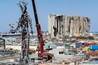 """A 25-metre-tall steel sculpture dubbed """"The Gesture"""" made from blast debris hangs from a crane near the devastated grain silos at Beirut port"""