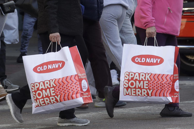 People carry shopping bags while crossing a street in San Francisco, Friday, Nov. 29, 2019. Black Friday once again kicked off the start of the holiday shopping season. (AP Photo/Jeff Chiu)