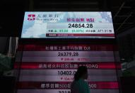A woman wearing face masks walks past a bank's electronic board showing the Hong Kong share index in Hong Kong Wednesday, July 29, 2020. Asian shares were mixed Wednesday as reports of dismal company earnings add to pessimism over the widespread economic fallout from the coronavirus pandemic.(AP Photo/Vincent Yu)