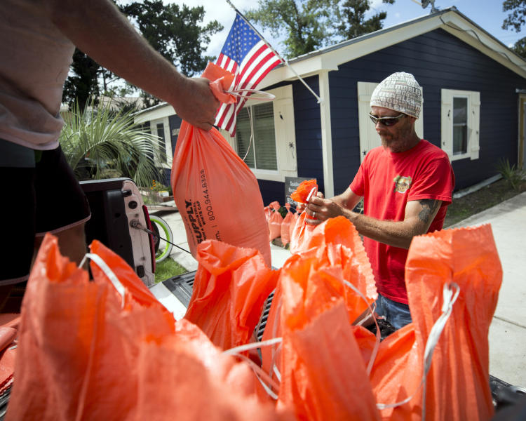 Tom Sikes, right, helps his friend Joey Spalding, left, fill sandbags at Spalding's home in Tybee Island, Ga., Tuesday, Sept. 3, 2019, before the potential arrival of Hurricane Dorian. Spalding's home was flooded by Hurricane Irma last year when he got three feet of water from the storm surge. (AP Photo/Stephen B. Morton)