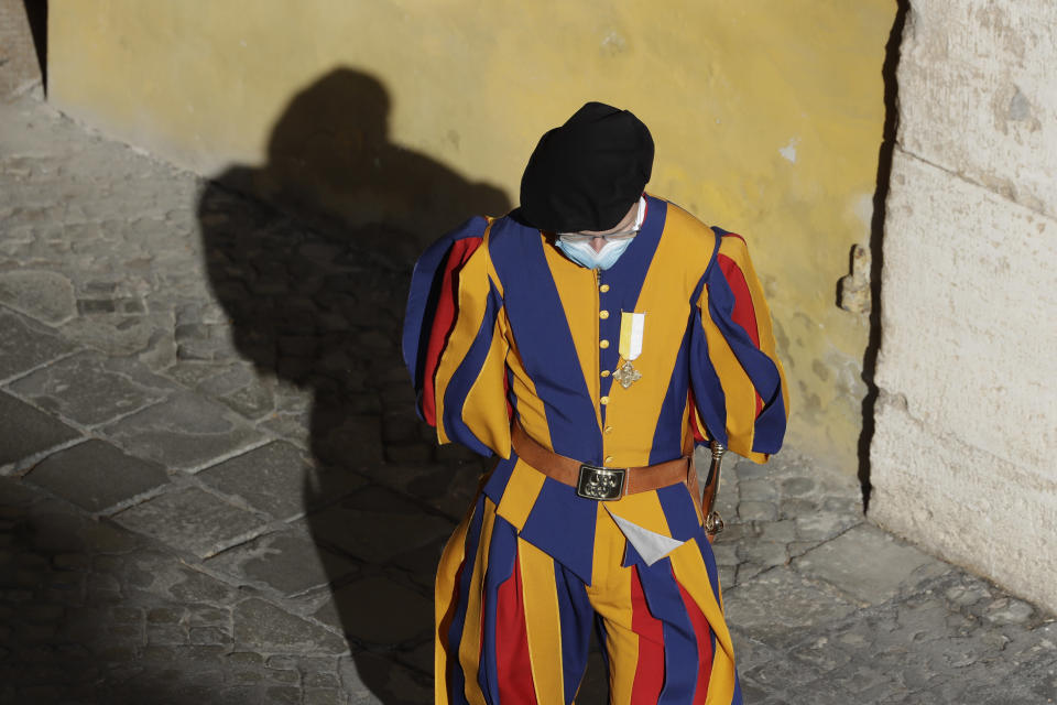 FILE - In this Sept. 2, 2020 file photo, a Vatican Swiss Guard wears a face mask to prevent the spread of COVID-19 in the San Damaso courtyard ahead of Pope Francis' general audience, the first with faithful since February when the coronavirus outbreak broke out, at the Vatican. On Monday, Oct. 12, 2020, the Vatican said in a statement that four Swiss Guards have tested positive for the coronavirus, as the surge in infections in surrounding Italy enters the Vatican walls. (AP Photo/Andrew Medichini, file)