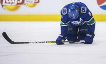 Vancouver Canucks' Chris Tanev kneels on the ice after blocking a shot during the first period of the team's NHL hockey game against the New Jersey Devils on Friday, March 15, 2019, in Vancouver, British Columbia. (Darryl Dyck/The Canadian Press via AP)