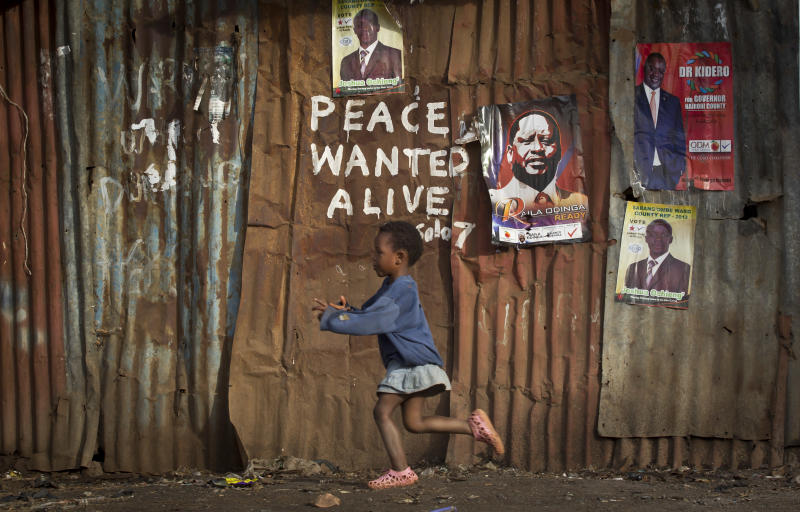 FILE - In this Wednesday, March 6, 2013 file photo, a young girl runs past pro-peace graffiti written during the post-election violence of the previous election in 2007 and a poster of presidential candidate Raila Odinga, center-right, in the Kibera slum of Nairobi, Kenya. Kenya's Supreme Court, who announced its ruling in late March but on Tuesday, April 16, 2013 released its 113-page written decision, says the execution of the nation's March presidential election wasn't perfect but that petitions to overturn the result did not prove President Uhuru Kenyatta was illegally elected. (AP Photo/Ben Curtis, File)