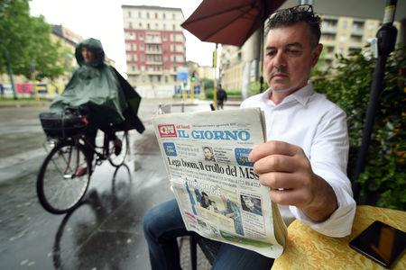 A man reads a newspaper with news of the rise of the far-right League party in Sunday's European parliamentary election, in Milan, Italy, May 27, 2019.  REUTERS/Guglielmo Mangiapane