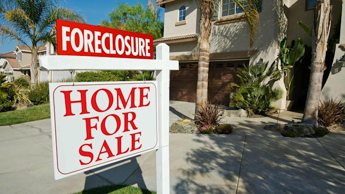 foreclosure sign in front of home for sale