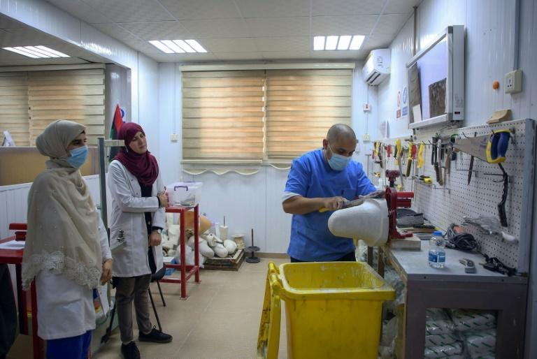 Ortho-prosthetist Badreddine Moftah builds plaster sockets to cover stumps of amputees, as students watch