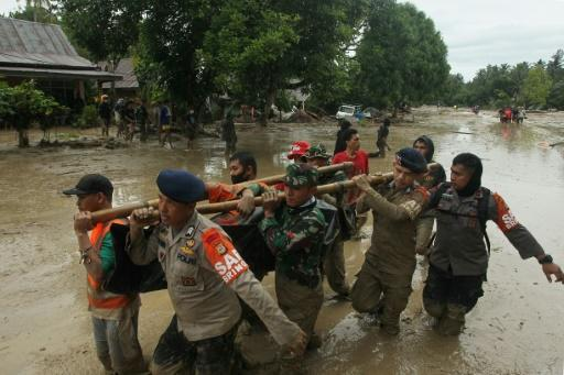 Rescuers carry a body recovered after flash floods in South Sulawesi which killed at least 15 people